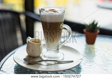hot fresh latte coffee cream in see through glass and white shinning latte coffee in pot with silver spoon on glass table at coffee time pourred already/ hot fresh coffee