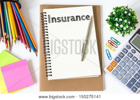 insurance text message on white paper and office supplies, pen, paper note, on white desk , copy space / business concept / view from above, top view