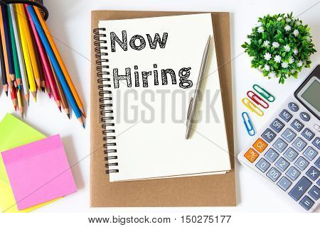 Now hiring text message on white paper and office supplies, pen, paper note, on white desk , copy space / business concept / view from above, top view