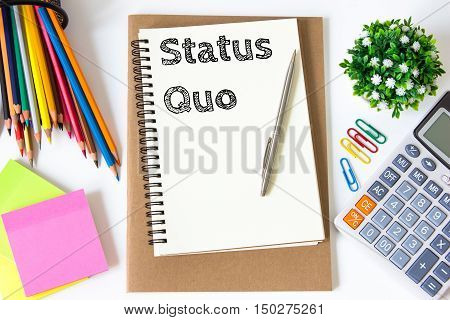 status quo text message on white paper and office supplies, pen, paper note, on white desk , copy space / business concept / view from above, top view