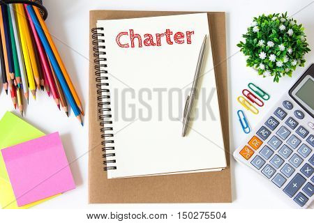 charter text message on white paper and office supplies, pen, paper note, on white desk , copy space / business concept / view from above, top view