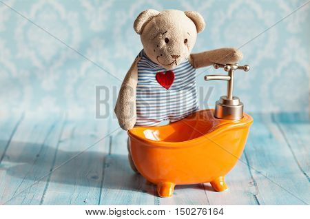 children's soft toy teddy bear is bathed in orange bath doll house. Blue bathroom to bear. Playing with dolls in the family. To bathe in the bathroom.