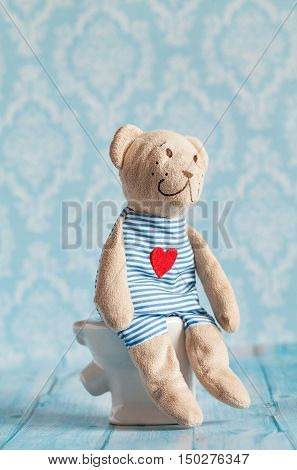 children's soft toy teddy bear toy sitting on the toilet in the doll house. Blue bathroom to bear. Playing with dolls in the family. Digestive problems, food poisoning.