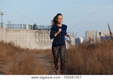 young adult woman running outdoors on a cold fall day