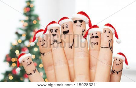 family, holidays, christmas and body parts concept - close up of fingers with smiley faces and santa hats over tree lights background