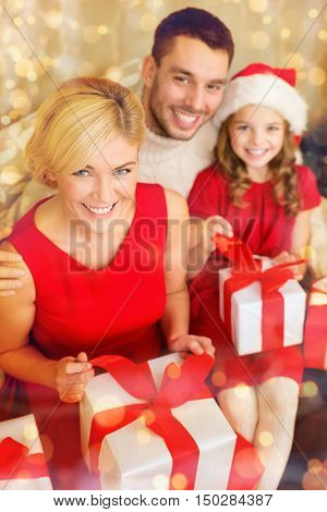 family, christmas, x-mas, winter, happiness and people concept - happy family opening gift boxes