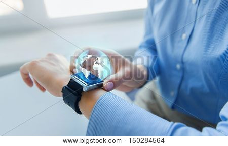 business, technology, network, communication and people concept - close up of woman hands setting smart watch with earth globe hologram at office