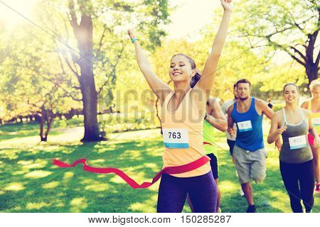 fitness, sport, victory, success and healthy lifestyle concept - happy woman winning race and coming first to finish red ribbon over group of sportsmen running marathon with badge numbers outdoors