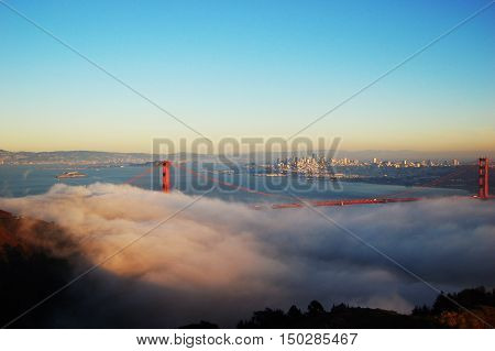 Golden Gate Bridge in fog in a winter dusk, with San Fransisco in the back ground, San Francisco, California, USA.