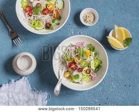 Rice noodles and vegetables salad. Healthy vegetarian food. On a blue background top view