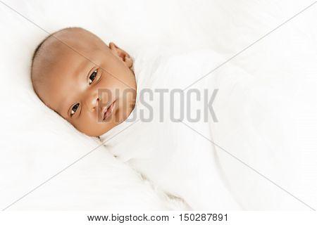 Three weeks old baby sleeping on white blanket cute infant newborn lying down close up shot eyes open
