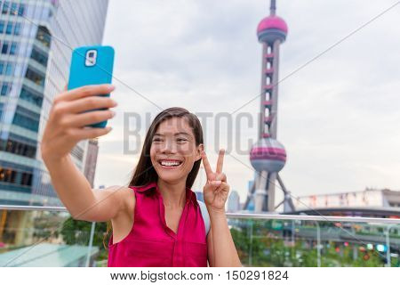 Asian tourist girl taking a selfie smartphone picture at a famous Shanghai landmark in the financial district of Pudong in China. Chinese woman doing a stereotypical japanese v sign for phone photo.