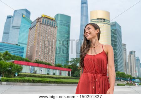 Shanghai woman walking in Pudong by huangpu river with view of the business district. Tourist or casual girl in beautiful red dress enjoying walk at Pudong boardwalk.