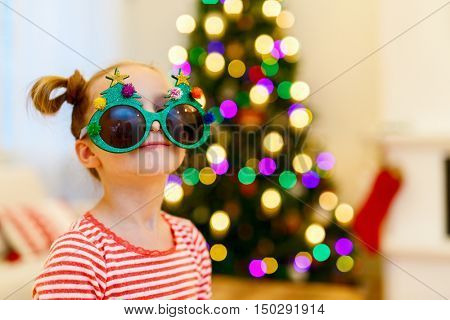 Adorable little girl wearing funny Christmas glasses in home beautifully decorated with Christmas tree and lights