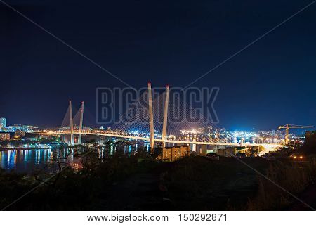 Night view of the bridge in the Russian Vladivostok over the Golden Horn bay.