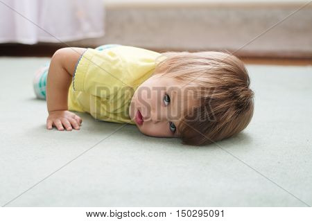 Little Caucasian kid lying on the carpet looking straight