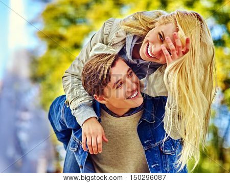 Young couple hugging and flirting in fall park . Beautiful happy blond girl with long hair hugging her favorite guy in fall park.