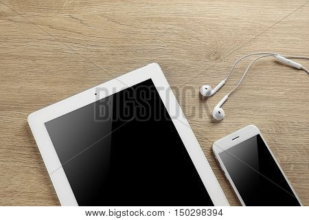 Tablet, smartphone and earphones on a table, close up