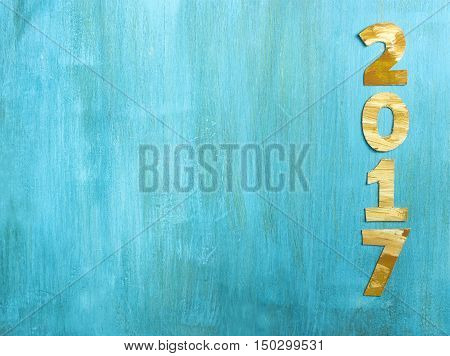 Photo of numbers forming '2017', cut out of paper with golden and white paint strokes, shot from above on vibrant turquoise background. New Year greeting card or annual report design template