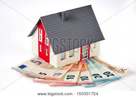 Money euro banknotes and figurine house red and white