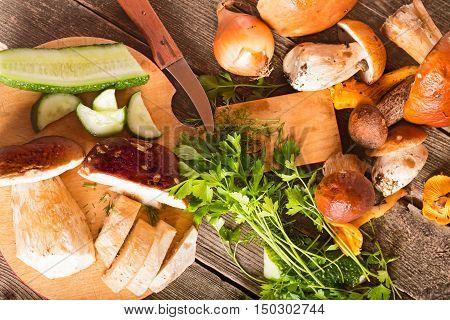 Mushrooms fresh verdure and vegetables on a chopping board. The top view close up small depth of sharpness
