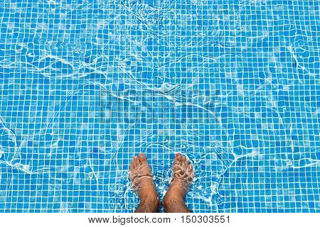 Bare feet cooling off in the pool relaxing concept
