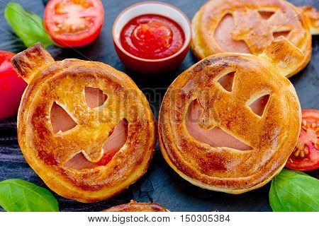 Funny Halloween pizza or mini pie in the shape of smiling Jack Lantern