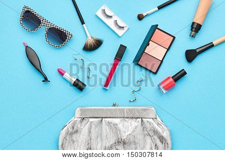 Fashion Cosmetic Makeup. Woman Beauty Accessories Set. Essentials. Fashion Design. Lipstick Brushes Eyeshadow, fashion Glamor Stylish Silver Clutch. Minimal Concept. Top view.Cosmetic Overhead
