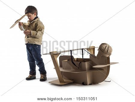 Young aviator assembles cardboard plane. Making airscrew.