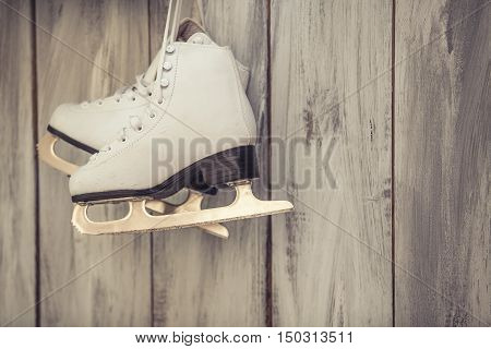 Skates white womens hang over the laces on the wooden wall retro