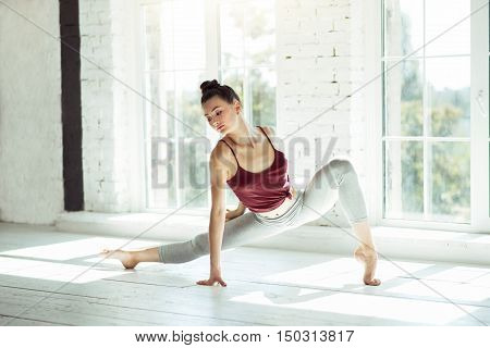 To reach a split. Beautiful active motivated girl working in a gym and doing exercise while stretching her legs to have a split.