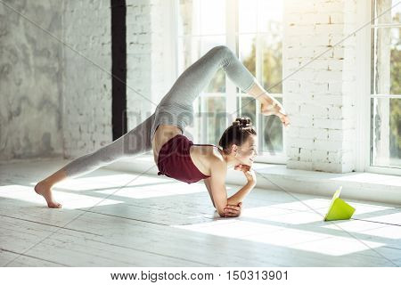 Relax and be flexible. Beautiful active young girl doing a yoga posture while reading and spending her time in a gym.