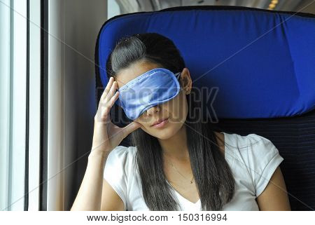 Woman resting on train cabin seat wearing eyes mask.