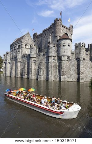 Ghent, 27 august 2016: tourist boat full of colorful people on river near Gravenstein Castle in belgian medieval city centre of Ghent