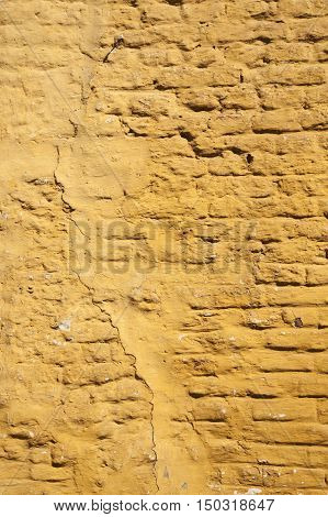 vertical part of ochre yellow painted brick wall