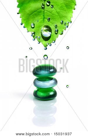 balancing spa shiny stones with leaf and water drops isolated on white