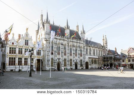 Bruges, Belgium 28 august 2016: city hall of belgian town bruges in flanders on sunny summer morning with people biking and walking