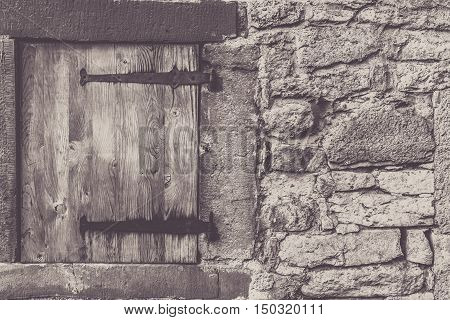 Aged wooden trap door - Architectural frame with a weathered wooden trap door and the stone wall from a traditional german house