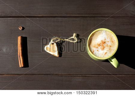 flat layout with a frothy coffee with cinnamon and gingerbread in the form of heart / my favorite aromatic and sweet breakfast