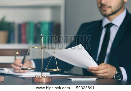 Scales of justice and businessman sitting at table