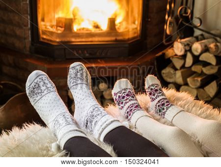 Warming and relaxing near fireplace. Woman and child feet in front of fire.