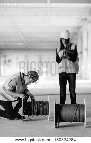 Engineers Checking Cables On Construction Site