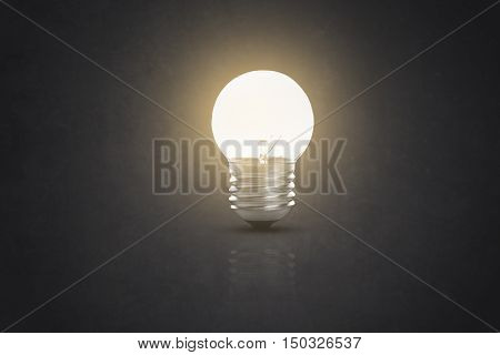 lit glowing yellow tungsten light bulb on black background.