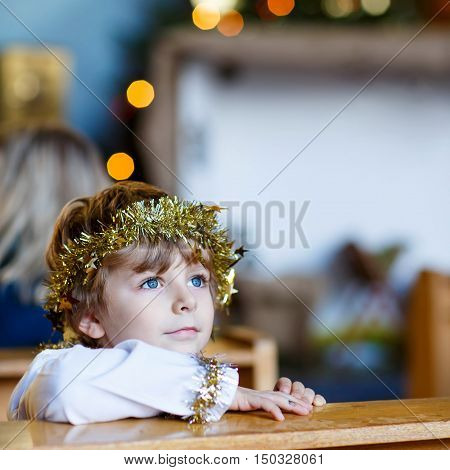 Beautiful little kid boy playing an angel in Christmas story in a church. Happy adorable blond child with lights and xmas tree on background.