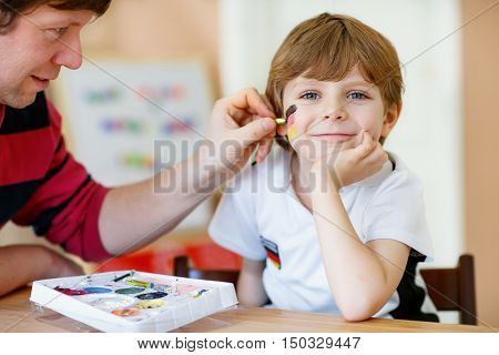 Father painting flag on face of little son for football or soccer game. Kid boy fan happy about game of team in champions league. Selective focus