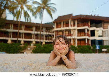 Smiling little girl lying on the beach
