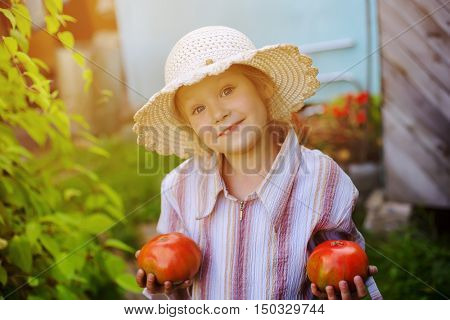 Little happy girl with tomato in the hands