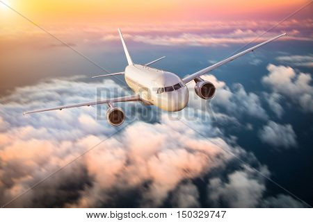Commercial airplane flying above clouds in dramatic sunset light