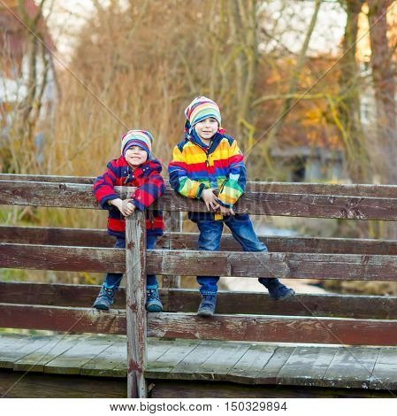 Two funny little kid sibling boys and friends in colorful clothes standing on bridge on spring day. Children having fun together, autumn or spring. Happy, joyful family