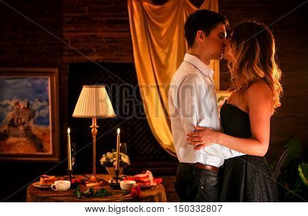 Luxary home interior. Couple in love dancing and kissing into luxary restaraunt. Romantic evening interior for loving couple. A lot of pictures in room.